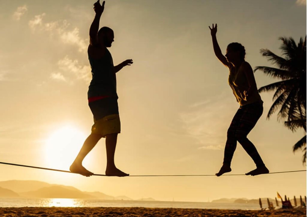 two people walking on slackline