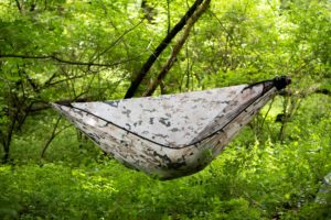 a person hanging in a chameleon hammock in the woods
