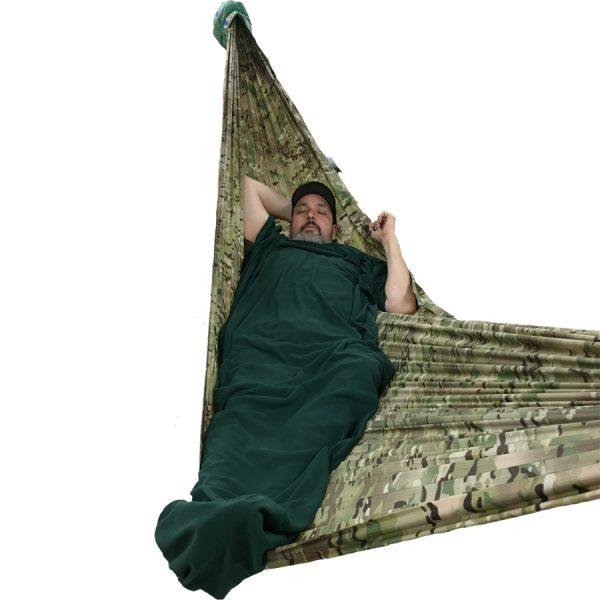 person laying in camo hammock