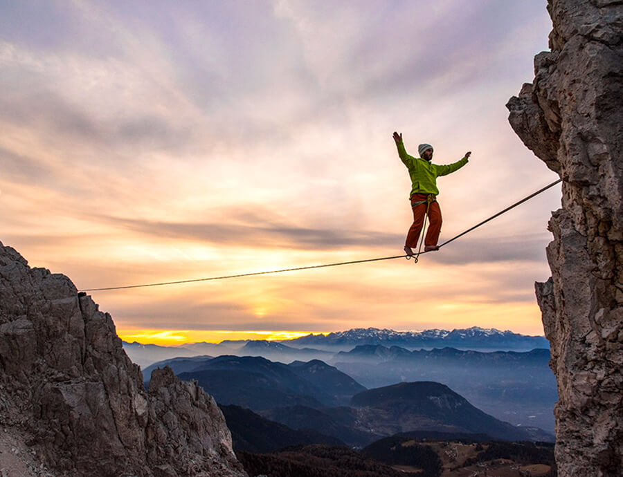 person walking slackline in mountains