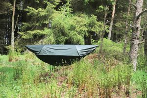 folded green tent in forrest
