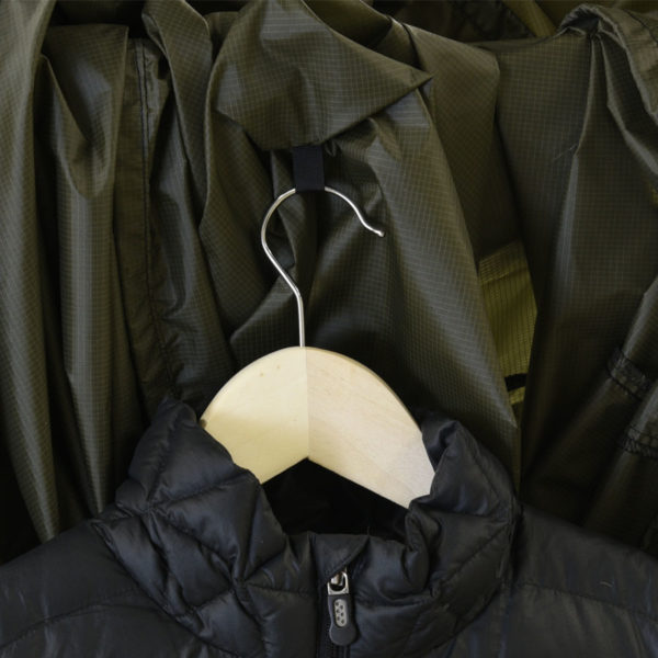 green garment bag with wooden hanger and black jacket