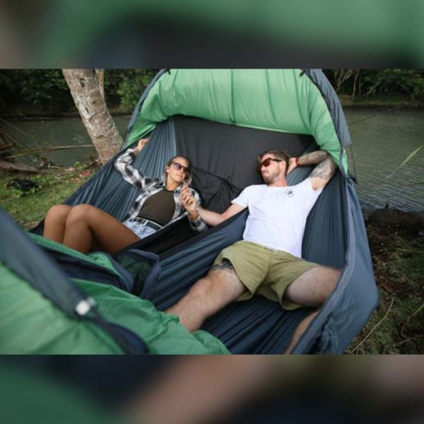 a man and a woman laying down in a double person camping hammock