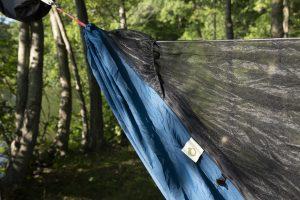 a lightweight camping hammock hung by a lake