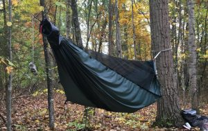 a camping hammock hung in the woods