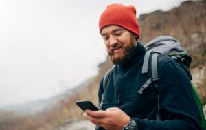 guy hiking in mountain with trail app